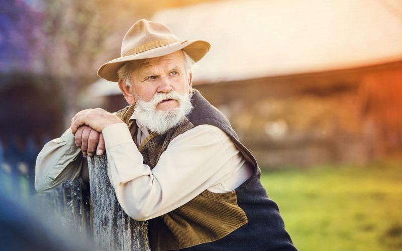 Rentner an Zaun gelehnt, Corona und Rentner