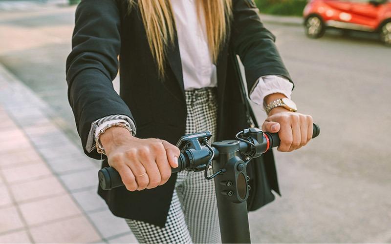 Frau fährt E-Scooter